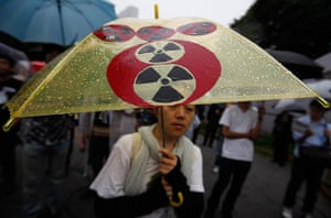 Japan nuclear protests: A protester holding an umbrella with altered Tokyo Electric Power Co logo