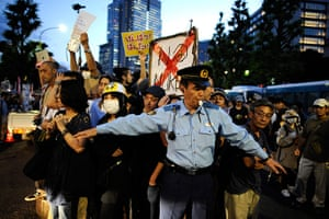 Japan nuclear protests: A policeman struggles to contain protesters during a anti-nuclear rally