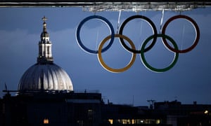 St Paul's cathedral and the Olympic rings hanging from Tower Bridge on 19 July 2012.