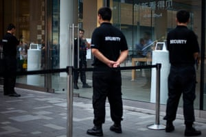 Picture desk live: Security workers guard an entrance of an Apple store Beijing