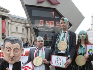Protesters pose by the Olympic countdown clock in Trafalgar Square on 20 July 2012. Photograph: Neil Hall/Reuters