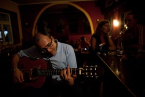 From the agencies: Jose Manuel Abel plays a guitar in the restaurant where he works