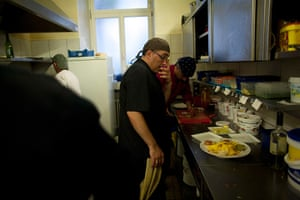 From the agencies: Jose Manuel Abel looks helps prepare plates of food while working