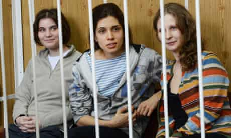 Members of punk band Pussy Riot sit behind bars during their court hearing in Moscow
