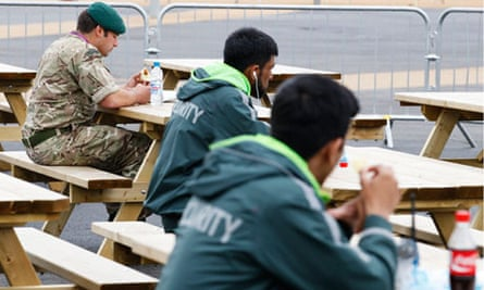 A soldier eats his lunch next to two G4S security guards