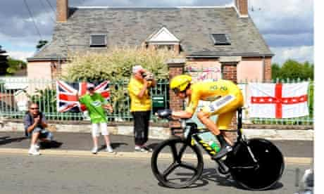Bradley Wiggins in yellow passes house with English and British flags