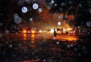 Beijing flooding: A woman wades through a flooded street