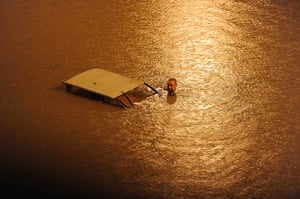 Beijing flooding: A man pushes his motor tricycle in a flooded street