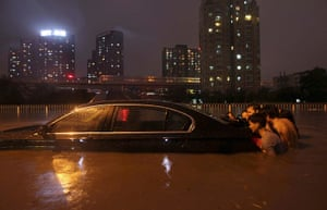 Beijing flooding: People push a stranded car through a flooded street
