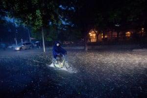 Beijing flooding: A cyclist rides through a flooded street