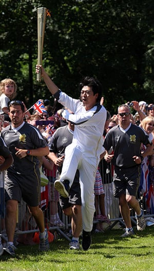 Olympic Torch 65: Lang Lang carrying the Olympic Flame on the Torch