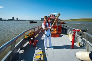 Olympic Torch 65: Aaron Reynolds carrying the Olympic Flame on a London Fire Brigade Boat