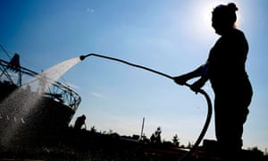 Olympic workers water the grass outside the Olympic Stadium on yesterday.