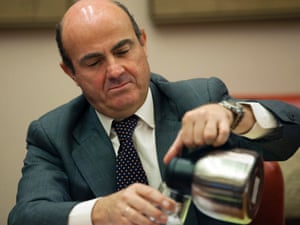 Spain's Economy Minister Luis de Guindos pours himself coffee at the start of a parliamentary hearing at the Spanish parliament in Madrid July 23, 2012.