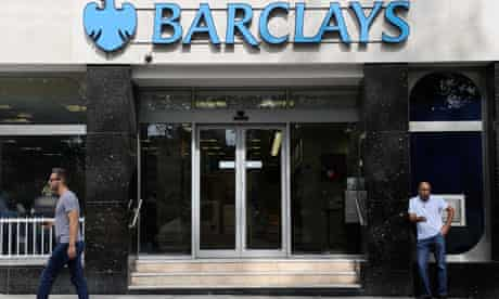 A man walks past a branch of Barclays bank in central London