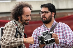 Hipster Olympics: An attendee shows another his Polaroid Land Camera