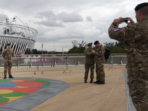 A soldier has his photograph taken in front of the Olympic Stadium in London on 19 July 2012. Photograph: Carl Court/AFP/Getty Images