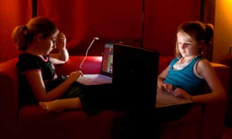Two young girls sisters both using laptop computers to chat with their friends