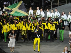 Usain Bolt carries the flag as he leads his country out