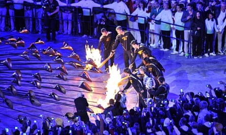 A group of seven young athletes light the Olympic Cauldron