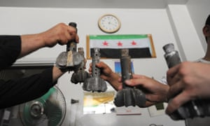 Syrian rebel fighters in Aleppo hold up regime fired mortar shells