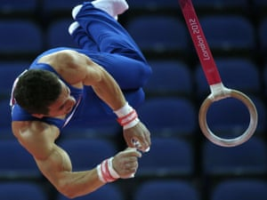 Rows of empty seats are visible at the North Greenwich Arena as France's gymnast Gael da Silva competes on the rings