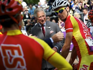 At least Prince Charles looks like he's enjoying himself as he greets cyclists at the start of the road race