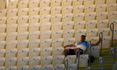 A spectator sits alone on the first day of Olympic swimming at the Aquatics Centre, east London