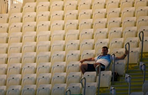 Olympics seating: A spectator sits among empty seats at the Aquatic centre