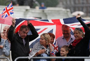 Women's road race: Supporters of the British cyclists shelter under a Union flag