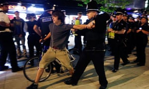 An officer grapples with a cyclist after a Critical Mass protest outside the Olympic park