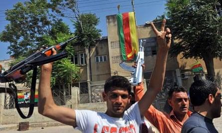 Syrian Kurds hold their rifles,