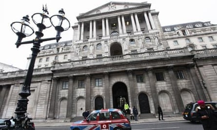 A taxi drives past the front of the Bank of England in London's financial district