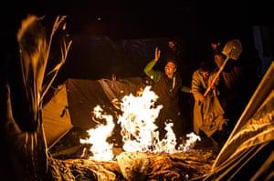 FTA: Daniel Berehulak: Men put out a fire, after some kerosene spilled onto a tent, at a campsite