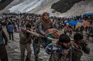 FTA: Daniel Berehulak: A Hindu pilgrim is carried on a palanquin over a glacier