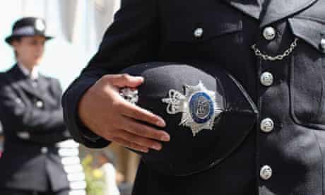 Metropolitan police officer holds his helmet