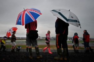 Rain: Spectators stand in the rain during the