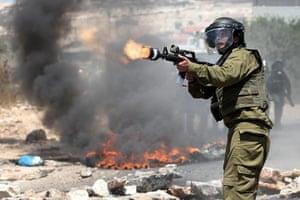 Picture desk live: An Israeli border policeman fires teargas