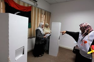 Libya Elections: An election commission worker tells two Libyan women to use separate booths