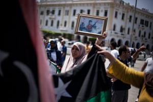 Libya Elections: A Libyan woman holds a framed photograph of a person killed in the uprising