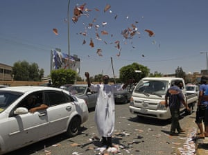 Libya Elections: A Libyan demanding greater representation throws torn ballots in the air