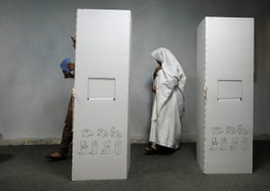 Libya election: A woman walks past a ballot booth at a polling station in Tripoli