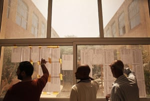 Libya election: Men look for their names on a voters list at a polling station in Tripoli
