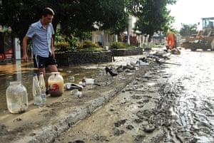 Russia Floods: A man walks in a flooded street in Krymsk