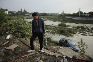 Russia Floods: A man walks past a submerged car on a flooded street in Krymsk