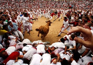 24 hours: Pamplona, Spain: A bull jumps over revellers in a bullring