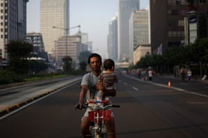 24 hours: Jakarta, Indonesia: A father holds his child while riding a bicycle