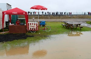 Summer rain: A man selling Pims sits in the rain at Silverstone circuit