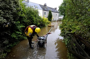Summer rain: A member of the fire services mans the pump outside a property