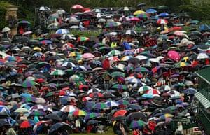 Summer rain: Tennis fans shelter from the rain at Wimbledon